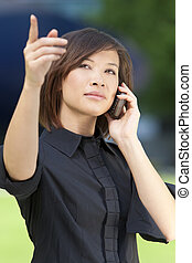 A beautiful young oriental Asian Chinese woman chatting on her cell phone and pointing.