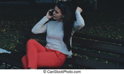 A beautiful young professional woman is having a phone conversation, outdoors in the city at night. She is smiling