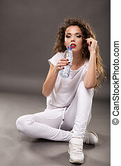 A beautiful young woman drinking from a water bottle