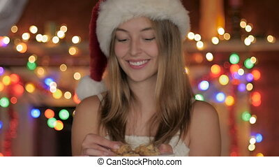 A beautiful young woman eats a chocolate chip cookie during Christmas