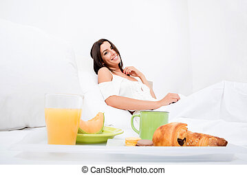 A beautiful young woman having breakfast in bed