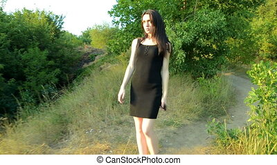 a beautiful young woman in a black dress walking down the street