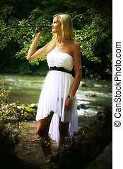 A beautiful young woman in a radiant white summer dress posing in a forest landscape with a river