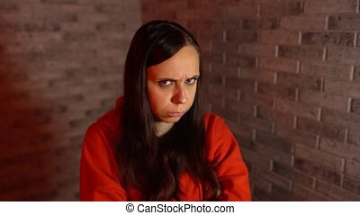 A beautiful young woman in a red hoodie is being in bad mood...