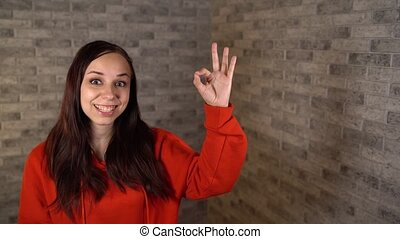 A beautiful young woman in a red hoodie shows is smiling and...