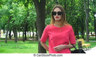 young woman in sunglasses and a red suit walks in the Park