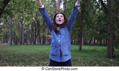 A beautiful young woman in the autumn park throws the fallen...