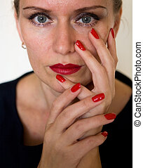 A beautiful young woman is touching her face with her fingers.