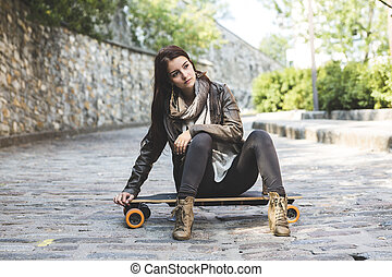 Beautiful young woman posing with a skateboard