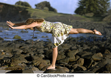 A beautiful young woman practices yoga on a the beach