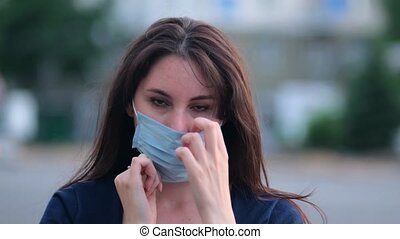 beautiful young woman puts on a mask on the street. Quarantine
