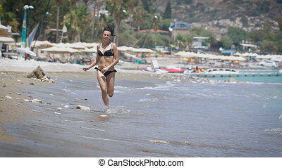 A beautiful young woman running at a beach in Cyprus.