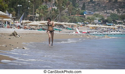 A beautiful young woman running at a beach in Cyprus. A sexy...