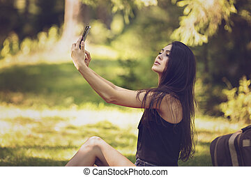 a beautiful young woman sitting at a picnic in nature and uses the phone