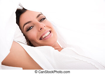A beautiful young woman under the sheets in the bed
