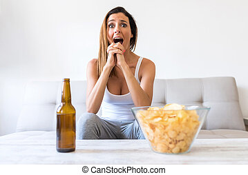 A beautiful young woman watching passionately something on a Scr