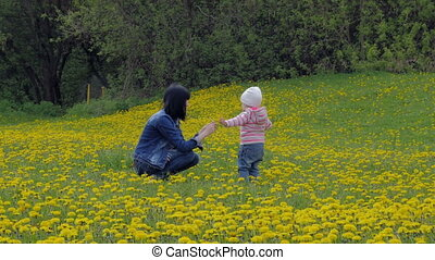 A beautiful, young woman with a child is walking in a city park. Mother and daughter are walking around the field with dandelions. Happy childhood