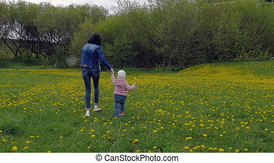 A beautiful, young woman with a child is walking in a city park. Mother and daughter are walking around the field with dandelions. Slow motion