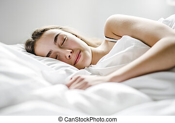 beautiful young woman with long hair sleeping on bed in bedroom
