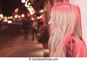 A beautifull girl with red light on the street.