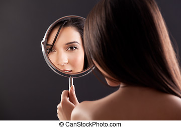 a beauty image of a young woman looking into a mirror, smiling.