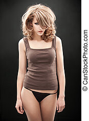 a beauty portrait of a young, blonde woman, wearing a 1960's make-up and hairstyle and a brown top with black underwear