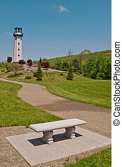 A bench in a park with a lighthouse in the background