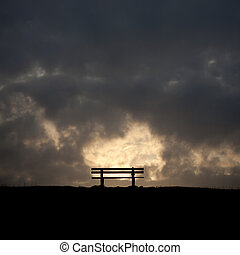 bench in the sunset on a dike at the northsea - a bench in ...