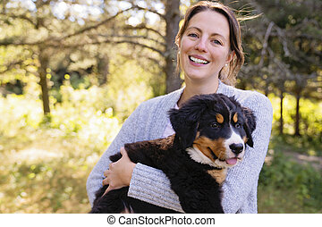 Bernese Mountain Dog puppy with his owner standing in forest park