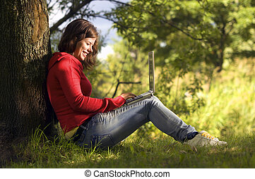 A beutiful student girl working on her laptop outdoor at sunny day