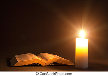 a bible on the table in the light of a candle