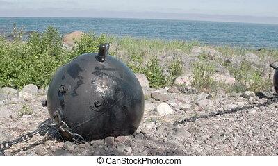 A big black sea mine on top of a hill near the sea. Under...