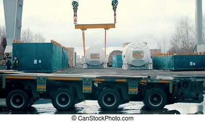 A big cargo lifting machine - transportation truck passing by on the foreground