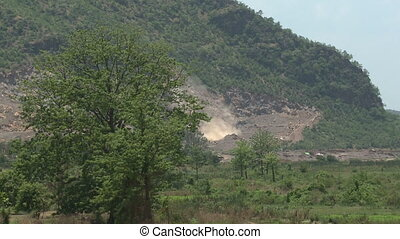 A big dust rising from the foot of a hill - A close up shot ...