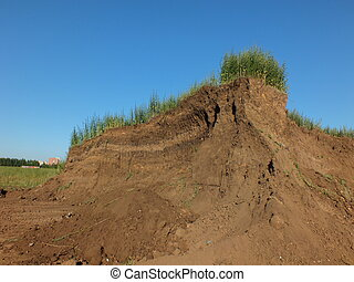 A big earth heap with grass on it