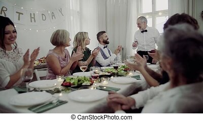 A big family sitting at a table on a indoor birthday party,...