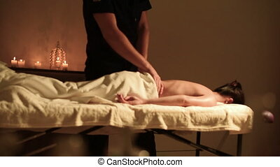 A big guy massage therapist does a massage for a young girl...