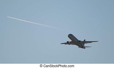 A big passenger plane flying away in the sky. Mid shot