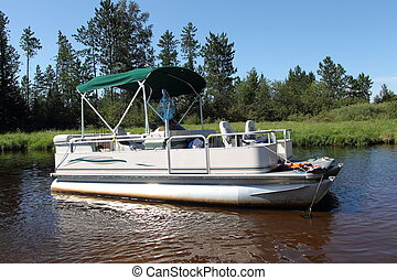 A big pontoon boat anchored in the river with fishing poles and the canopy up.