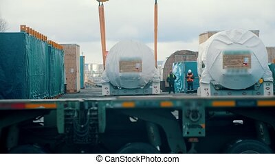 A big shipping truck riding on the construction site - men working on the background