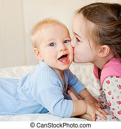A big sister kisses her little brother