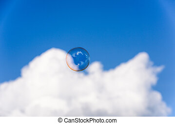 A big soap bubble flying up into the blue sky