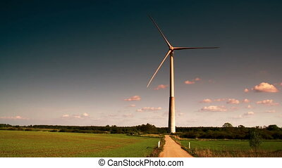 A big windmill on standby on a green field FS700 Odyssey 7Q...