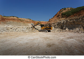 A big yellow excavator on a new construction site on the blue sky and sandy quarry background. Copy space. Copy space.