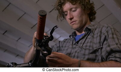 A bike mechanic attaches a cable to a gear shifter - low...