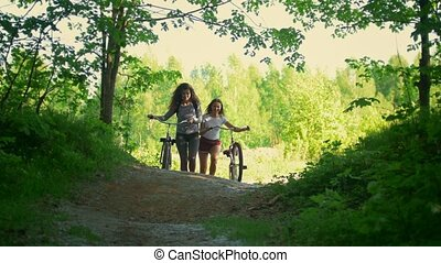 A bike ride in the forest, two girlfriends of the cyclist have fun communicating and climb from the clearing to the path