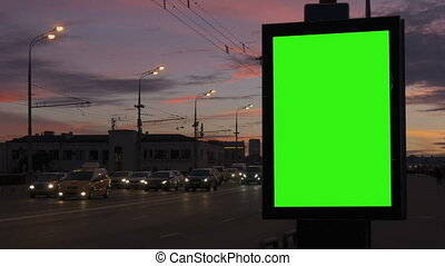 A Bilboard with a Green Screen on a Busy Street.