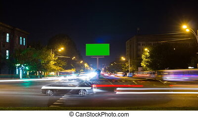 A billboard with a green screen on a background of city traffic with long exposure. Time Lapse. The camera is approaching
