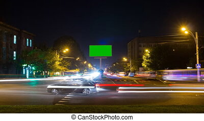 A billboard with a green screen on a background of city traffic with long exposure. Time Lapse.