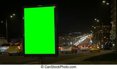 A Billboard with a Green Screen on a Busy Street. Blurred background of lights and cars.